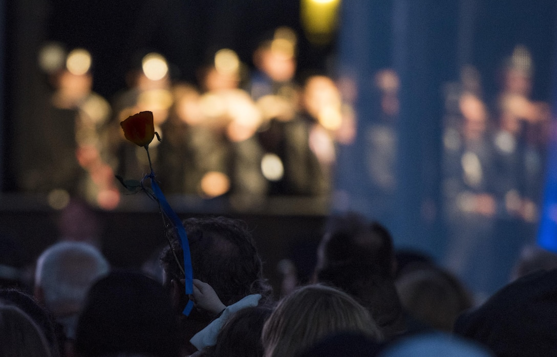 A survivor of a fallen police officer raises a single rose during the 29th Annual Candlelight Vigil honoring fallen police officers from around the country on the National Mall in Washington, D.C., May 13, 2017. Approximately 300 police officers' names were read, engraved into the National Police Memorial. Among those names was Staff Sgt. James D. McNaughton, a U.S. Army Reserve military police who was the first New York City police officer killed in action while deployed to Iraq, Aug. 2, 2005. (U.S. Army Reserve photo by Sgt. Audrey Hayes)