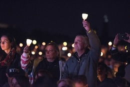 William and Michele McNaughton from, Centereach, New York, raise lit candles as their son's name, Staff Sgt. James D. McNaughton, is read during the 29th Annual Candlelight Vigil on the National Mall in Washington, D.C., May 13, 2017. McNaughton was a U.S. Army Reserve military police who was the first New York City police officer killed in action while deployed to Iraq, Aug. 2, 2005. Approximately 300 police officers' names were read, engraved into the National Police Memorial. (U.S. Army Reserve photo by Sgt. Audrey Hayes)
