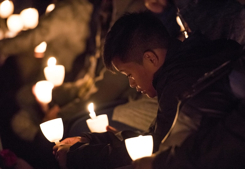 A survivor of a fallen police officer bows his head during the 29th Annual Candlelight Vigil honoring fallen police officers from around the country on the National Mall in Washington, D.C., May 13, 2017. Approximately 300 police officers' names were read, engraved into the National Police Memorial. Among those names was Staff Sgt. James D. McNaughton, a U.S. Army Reserve military police who was the first New York City police officer killed in action while deployed to Iraq, Aug. 2, 2005. (U.S. Army Reserve photo by Sgt. Audrey Hayes)