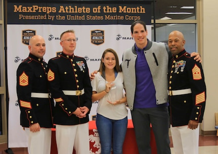 MGySgt. Ramon Gallimore, GySgt. Brian Wright and SSgt. Dalton Miller pose for a group photo with Eva Stahlschmidt after being presented the MaxPreps High School Athlete of the Month award at Steinbrenner High School, Lutz, Fl., May 10, 2017. MaxPreps Athlete of the Month awards are given to those few individuals who not only excel physically, but mentally and showcase overall good character. (Official U.S. Marine Corps photo by Sgt. Calvin Shamoon/ Released)