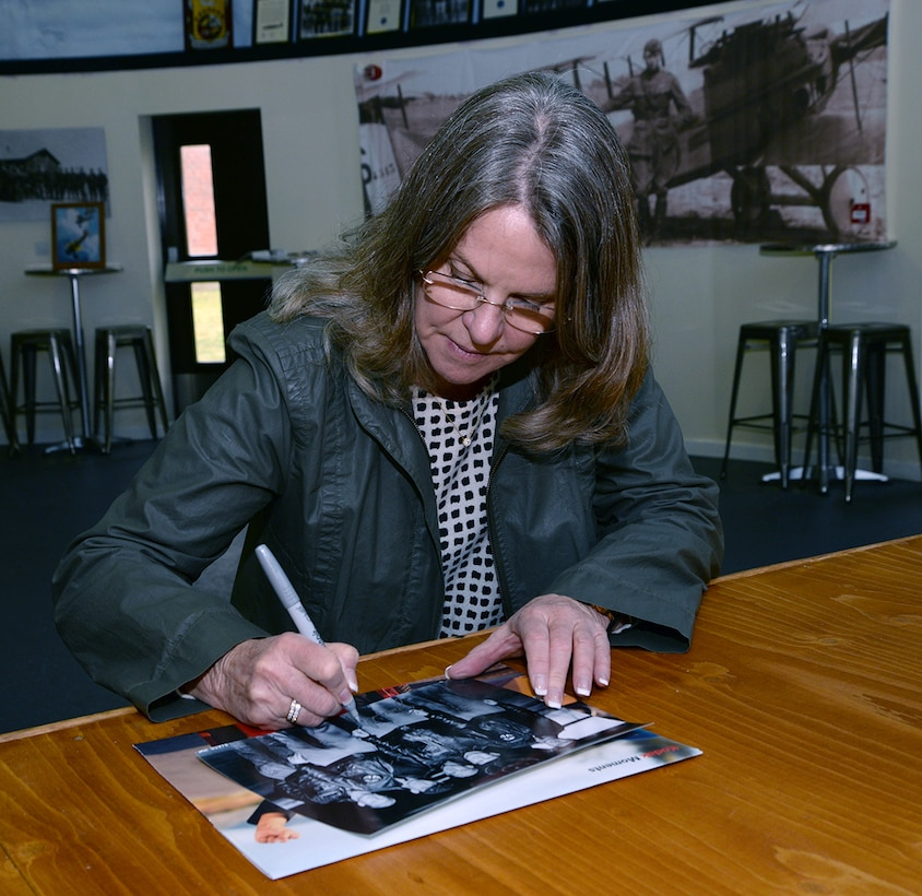 """Jonna Doolittle Hoppes, granddaughter of Gen. James Harold """"Jimmy"""" Doolittle, American aviation pioneer and retired lieutenant general in the U.S. Army Air Corps, signs a photo of her grandfather and some of his crew during a visit to the 95th Reconnaissance Squadron Heritage Hub. On April 18, 1942, then-Lt. Col. Doolittle led the daylight air raid on Tokyo after the Japanese attacked Pearl Harbor. His crew on that mission became known as the """"Doolittle Raiders."""" Hoppes visited RAF Mildenhall along with former World War II bases in East Anglia during the 100th Bomb Group Foundation visit to celebrate the 75th anniversary of the 100th Bomb Group. During World War II, six of the 16 Doolittle Raiders' crew were from the 95th Bomb Squadron. The 95th BS was redesignated the 95th RS in 1982. (U.S. Air Force photo by Karen Abeyasekere)"""