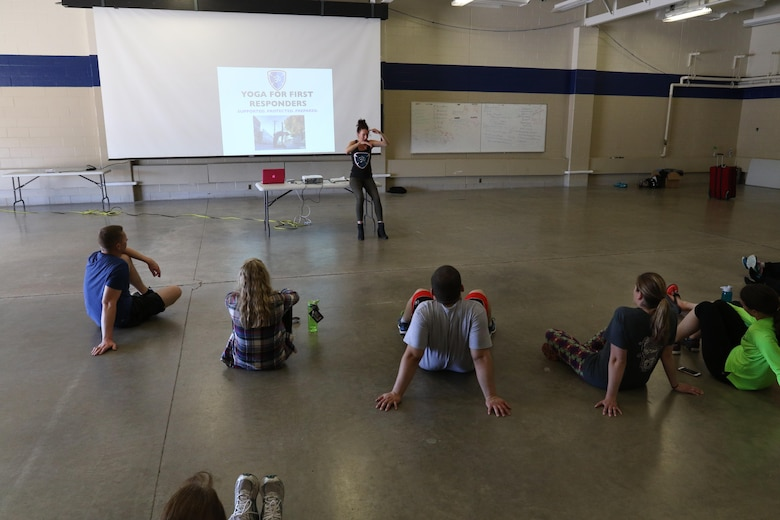 Olivia Kvitne, top, provides a lecture about the history and benefits of Yoga to members of the 103rd Sustainment Command (Expeditionary) on May 12, 2017 at Fort Des Moines, Iowa.  Kvitne is founder of Yoga for First Responders which focuses on providing Yoga as a tool to relieve stress for veterans and those who have experienced post-traumatic stress disorder.  (Released/U.S. Army photo by Capt. Charles An)