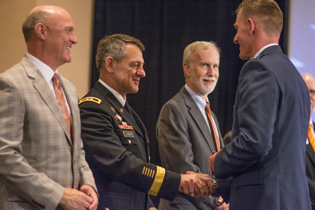 U.S. Army Maj. Gen. James B. Linder, commander of the U.S. Army John F. Kennedy Special Warfare Command, congratulates brand new 2nd Lt. Sean Mac Lain during Clemson University's Reserve Officers' Training Corps commissioning ceremony, May 10, 2017. Mac Lain was a member of both the 2016 Clemson Tigers National Football Championship team and the Clemson ROTC Pershing Rifles 2016 national champion drill and ceremony team. (U.S. Army Reserve photo by Staff Sgt. Ken Scar)