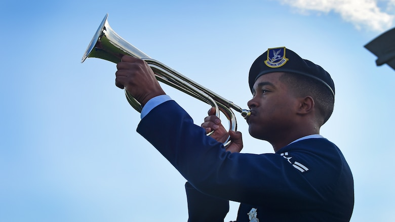 """U.S. Airman 1st Class Ramon Crespo, 633rd Security Forces Squadron patrolman, plays """"Taps"""" during the National Police Week opening ceremony at Joint Base Langley-Eustis, Va., May 15, 2017. Police Week is observed nationally to pay respects to both military and civilian law enforcement officers who have fallen in the line of duty. (U.S. Air Force photo/Staff Sgt. Areca T. Bell)"""