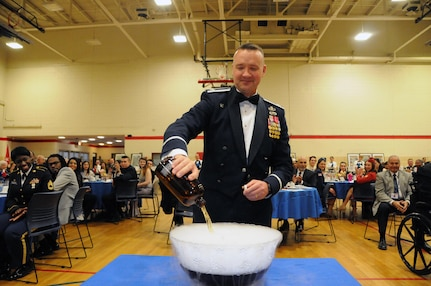"""Col. Frederick Thaden, commander of Joint Base McGuire-Dix-Lakehurst, New Jersey, pours an ingredient into the grog bowl during the U.S. Army Reserve's 99th Regional Support Command dining out May 12 on JBMDL.  The theme of the event was """"Veterans: Then and Now.""""  More than 100 veterans from area veteran homes were invited to attend."""
