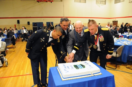 "Spc. Aaron Chavers (left) and John Ruszkai (second from right), a World War II veteran, help cut the cake May 12 during the U.S. Army Reserve's 99th Regional Support Command dining out on Joint Base McGuire-Dix-Lakehurst, New Jersey.  The theme of the event was ""Veterans: Then and Now.""  More than 100 veterans from area veteran homes were invited to attend.  Command Sgt. Maj. Almeida, command sergeant major for the 99th RSC, and Maj. Gen. Troy D. Kok, commanding general for the 99th RSC, are also pictured."