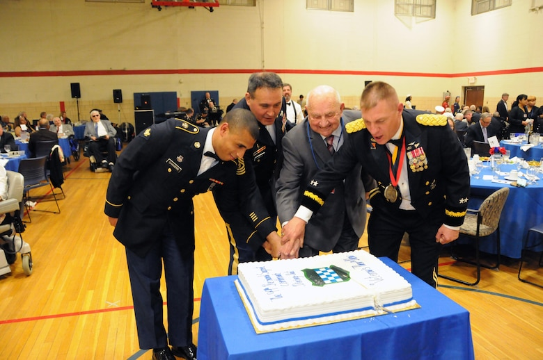 """Spc. Aaron Chavers (left) and John Ruszkai (second from right), a World War II veteran, help cut the cake May 12 during the U.S. Army Reserve's 99th Regional Support Command dining out on Joint Base McGuire-Dix-Lakehurst, New Jersey.  The theme of the event was """"Veterans: Then and Now.""""  More than 100 veterans from area veteran homes were invited to attend.  Command Sgt. Maj. Almeida, command sergeant major for the 99th RSC, and Maj. Gen. Troy D. Kok, commanding general for the 99th RSC, are also pictured."""