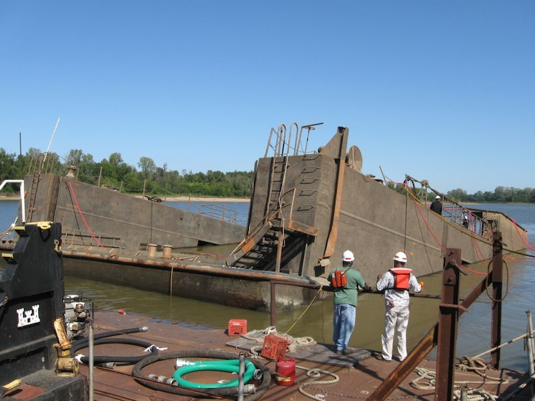 The bow of the Rouse submerged.   In 2008, the Rouse sank and was almost lost. On Sunday morning, July 20, a security guard noticed that one end of the Rouse's deck was sinking and alerted District employees. Crew arrived to find the west wall completely submerged. Initially, the crew raised the sinking end, but the dock sank again. The sinking was caused by two leaking valves that allowed water to enter the dock.  In October 2008, the Memphis District partnered with the Nashville District's Dive Team in an effort to recover the Rouse. The dive team made repairs with the help of EEY technicians who fabricated special parts needed to raise the Rouse.