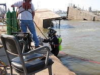 A diver descends into the Mississippi River as part of the Rouse recovery mission.  In 2008, the Rouse sank and was almost lost.  On Sunday morning, July 20, a security guard noticed that one end of the Rouse's deck was sinking and alerted District employees. Crew arrived to find the west wall completely submerged. Initially, the crew raised the sinking end, but the dock sank again. The sinking was caused by two leaking valves that allowed water to enter the dock.  In October 2008, the Memphis District partnered with the Nashville District's Dive Team in an effort to recover the Rouse. The dive team made repairs with the help of EEY technicians who fabricated special parts needed to raise the Rouse.