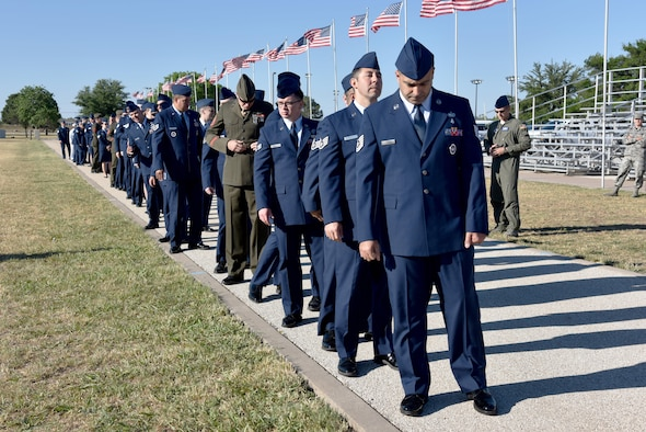 Service members earning their Community College of the Air Force degree wait in line before the CCAF graduation at the parade field on Goodfellow Air Force Base, Texas, May 12, 2017. Fifty-six Airmen, four Marines and a Sailor graduated the program that is the Air Force equivalent to getting an associate degree. (U.S. Air Force photo by Staff Sgt. Joshua Edwards/Released)