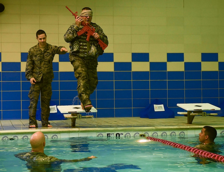 U.S. Air Force Tech. Sgt. Daniel Day, 633rd Security Forces flight chief, conducts water confidence training during a training evaluation at Joint Base Langley-Eustis, Va., April 28, 2017. To accomplish this training evolution, Day had to strip-off his combat vest and recover his weapon after jumping into the Shellbank Fitness Center pool blindfolded. (U.S. Air Force photo/Senior Airman Derek Seifert)