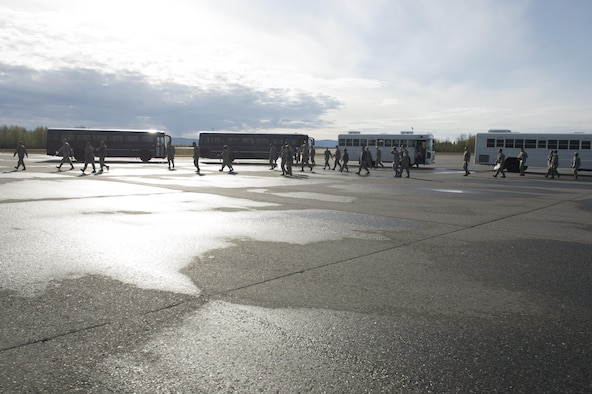 U.S. Air Force Airmen from the 354th Fighter Wing, depart buses on the flightline to assist with a foreign object debris (FOD) walk, May 15, 2017, at Eielson Air Force Base, Alaska. The Icemen Team worked together to ensure five and half miles of taxiways and runways were clear of debris. (U.S. Air Force photo by Airman Eric M. Fisher)