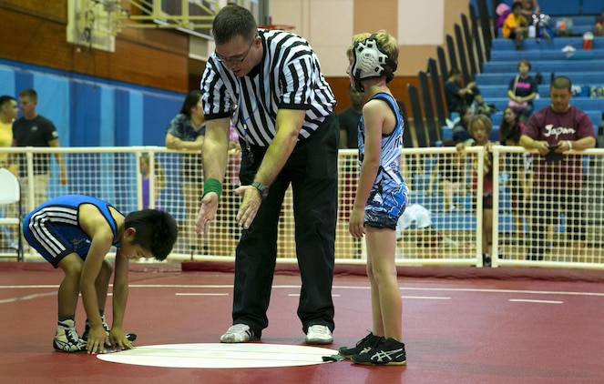 Navy Lt. David Keim referees youth wrestlers during the Okinawa Open Championship May 13 on Marine Corps Air Station Futenma, Okinawa, Japan. Approximately 100 wrestlers from the Okinawa Youth Wrestler League competed alongside 70 wrestlers from the Gladiator Wrestling League. The Okinawa Open Championship is the largest youth wrestling tournament in Okinawa. Keim is a chaplain who volunteers as a referee with the Gladiator Wrestling League. (U.S Marine photo by Lance Corporal Tayler P. Schwamb)