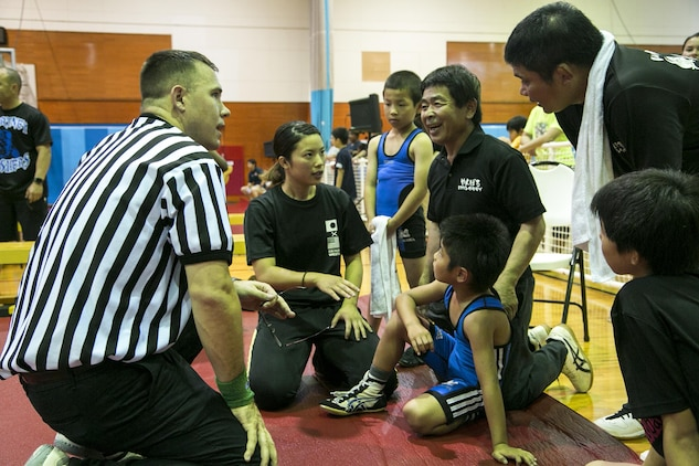 A Marine volunteer explains the rules for the Okinawa Open Championship to Yoshikazu Arakaki May 13 on Marine Corps Air Station Futenma, Okinawa, Japan. The wrestlers practice with two different fighting styles. The Okinawan Youth Wrestling League utilizes freestyle wrestling while the Gladiator Wrestlers utilize folk style. Arakaki is the coach for the Okinawa Youth Wrestling League. (U.S Marine photo by Lance Corporal Tayler P. Schwamb)