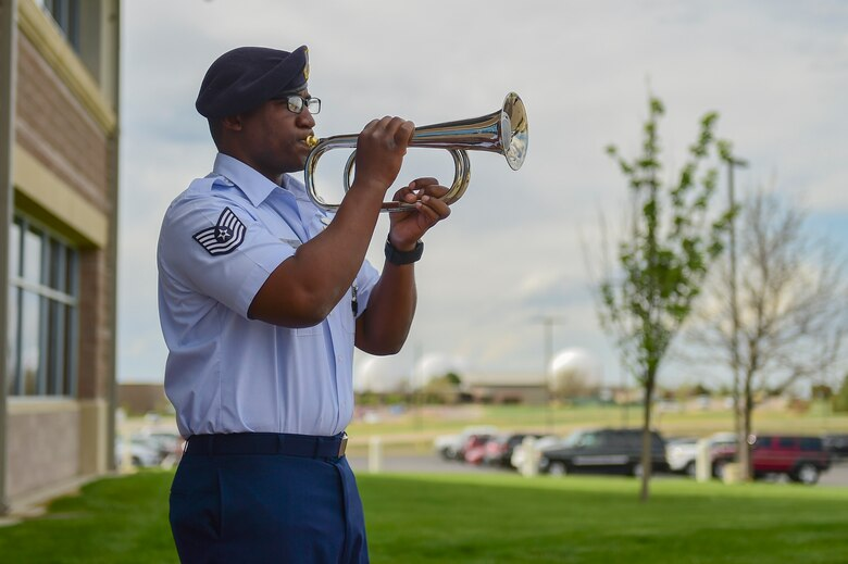 Tech. Sgt. Brandon Dinkins, 460th Security Forces Squadron trainer, plays TAPS during the Retreat ceremony May 15, 2017, on Buckley Air Force Base, Colo. The Retreat ceremony recognizes fallen civilian and military law enforcement officers with the 21-gun salute, the playing of TAPS and the National Anthem. (U.S. Air Force photo by Airman Jacob Deatherage/Released)