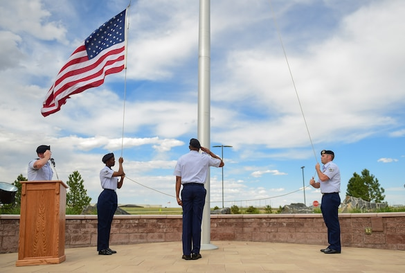 460th Security Forces Squadron Airmen render salutes as the American flag is lowered during a Retreat ceremony May 15, 2017, on Buckley Air Force Base, Colo. The Retreat ceremony recognizes fallen civilian and military law enforcement officers with the 21-gun salute, the playing of TAPS and the National Anthem. (U.S. Air Force photo by Airman Jacob Deatherage/Released)