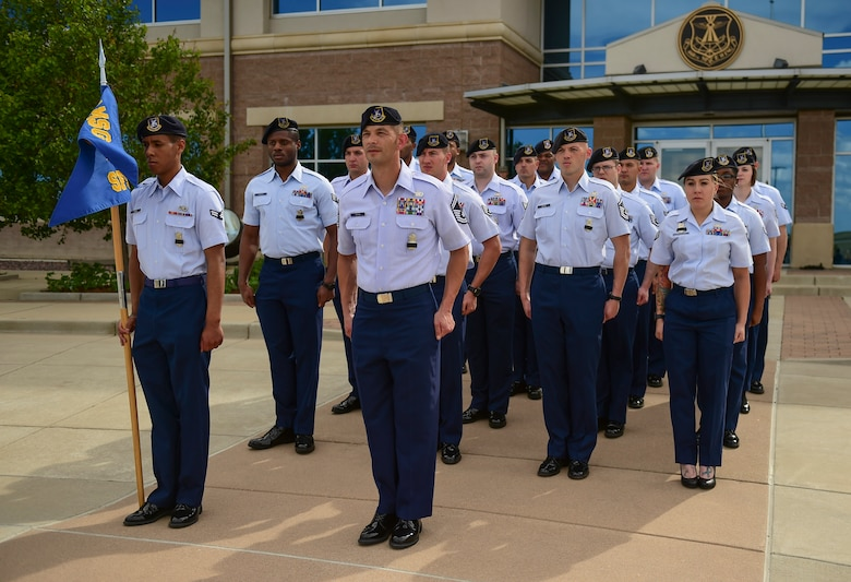 A flight of 460th Security Forces Squadron Airmen stand at attention during a Retreat ceremony May 15, 2017, on Buckley Air Force Base, Colo. The Retreat ceremony recognizes fallen civilian and military law enforcement officers with the 21-gun salute, the playing of TAPS and the National Anthem. (U.S. Air Force photo by Airman Jacob Deatherage/Released)
