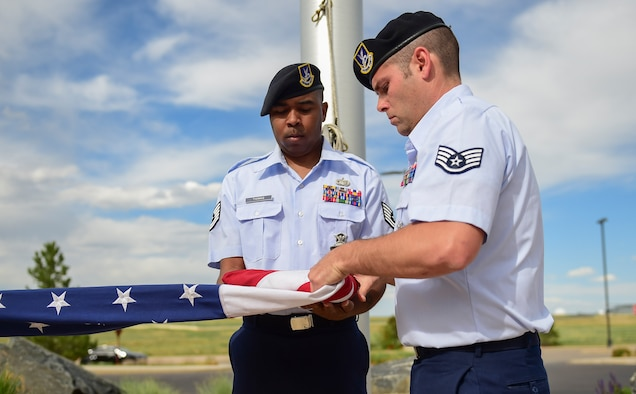 Tech Sgt. Michael Thomas, 460th Security Forces Squadron physical security NCO in-charge, and Staff Sgt. Daniel Leutwyler, 460th SFS resource protection NCO in-charge, fold the American flag May 15, 2017, during the Retreat ceremony on Buckley Air Force Base, Colo. The Retreat ceremony recognizes fallen civilian and military law enforcement officers with the 21-gun salute, the playing of TAPS and the National Anthem. (U.S. Air Force photo by Airman Jacob Deatherage/Released)