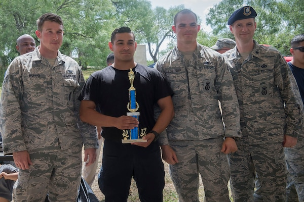 Members of the 343rd Training Squadron accept their first place trophy after competing in the Obstacle Course Team Challenge May 15, 2017, at Joint Base San Antonio-Lackland, Texas, Medina Annex. The event was held as part of National Police Week, an annual celebration to honor the service and sacrifice of law enforcement members and pays special tribute to law enforcement officers who have lost their lives in the line of duty for the safety and protection of others. JBSA security forces members participated participate in events weeklong May 15-19 across the installations. (U.S. Air Force photo by Staff Sgt. Marissa Garner)