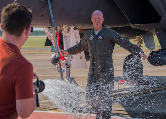 Brig. Gen. Christopher Azzano, 96th Test Wing commander, braces for a soaking while his son, Steven, hoses him down during his fini flight at Eglin Air Force Base, Fla. May 15. The fini flight is a symbol of a member's final flight with the unit or base. Azzano's new assignment will take him to Wright-Patterson Air Force Base in Ohio to take command of the Directorate of Air, Space and Cyberspace Operations. (U.S. Air Force photo/Ilka Cole)