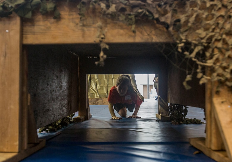 A child with the Young Marines program crawls under an obstacle while attending the Young Marine Battalion Field Meet on Camp Hansen, Okinawa, Japan, May 13, 2017. The field meet allowed local Okinawan children and children of the YMP to overcome obstacles and build camaraderie. (U.S. Marine Corps Photo by Lance Cpl. Deseree Kamm)