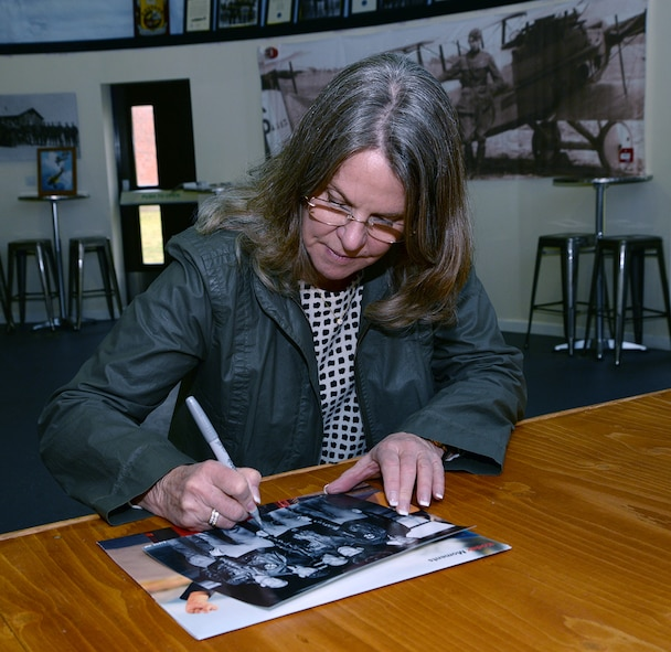 "Jonna Doolittle Hoppes, granddaughter of Gen. James Harold ""Jimmy"" Doolittle, American aviation pioneer and retired lieutenant general in the U.S. Army Air Corps, signs a photo of her grandfather and some of his crew during a visit to the 95th Reconnaissance Squadron Heritage Hub. On April 18, 1942, then-Lt. Col. Doolittle led the daylight air raid on Tokyo after the Japanese attacked Pearl Harbor. His crew on that mission became known as the ""Doolittle Raiders."" Hoppes visited RAF Mildenhall along with former World War II bases in East Anglia during the 100th Bomb Group Foundation visit to celebrate the 75th anniversary of the 100th Bomb Group. During World War II, six of the 16 Doolittle Raiders' crew were from the 95th Bomb Squadron. The 95th BS was redesignated the 95th RS in 1982. (U.S. Air Force photo by Karen Abeyasekere)"