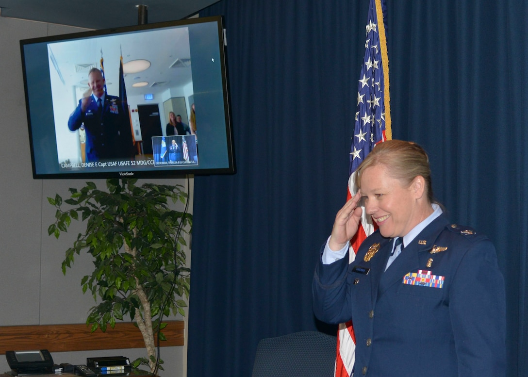 Col. Theresa Goodman, Air Force Inspectiion Agency medical inspector, salutes her brother, Col. Joseph McFall, 52nd Fighter Wing commander, during her promotion ceremony via video teleconferencing technology, May 15, 2017. Goodman is stationed at Kirtland Air Force Base, New Mexico, 5296 miles away from Spangdahlem.