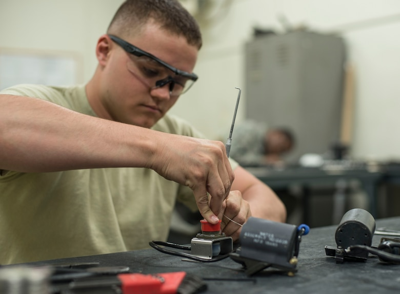 U.S. Air Force Senior Airman Joshua Wood, a 35th Maintenance Squadron armament technician, works on a clearing solenoid at Kunsan Air Base, Republic of Korea, May 15, 2017. Wood had to completely replace the clearing solenoid because it was damaged beyond repair. This piece of equipment places the round in the clearing cam path of a M61A1 20mm Gatling Gun. Every 18 months they completely break down the M61A1 and rebuild it, repairing or replacing any components. (U.S. Air Force photo by Senior Airman Brittany A. Chase)