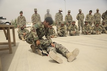 An Afghan National Army soldier with the Helmand Regional Military Training Center demonstrates proper application of a tourniquet to soldiers with the 2nd Kandak, 4th Brigade, 215th Corps at Camp Shorabak, Afghanistan, May 14, 2017. More than 600 soldiers from the unit are scheduled to begin an operational readiness cycle May 20, which is designed to enhance its warfighting capabilities. Approximately 15 Marine advisors with Task Force Southwest will provide recommendations for sustainment and improvement as part of the unit's train, advise and assist mission in Helmand Province. (U.S. Marine Corps photo by Sgt. Lucas Hopkins)