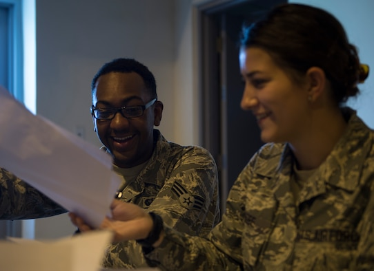 U.S. Air Force Senior Airman Jabari Superville, left, hands two shipping manifests to Senior Airman Airiana Magee, both with the 379th Expeditionary Force Support Squadron to ensures the invoice matches the shipment at Al Udeid Air Base, Qatar May 10, 2017. Each week, a small team of Airmen work together to review shipments of produce, making sure the numbers matches the quantity received and that the quality of the produce meets standards. (U.S. Air Force photo by Tech. Sgt. Amy M. Lovgren)