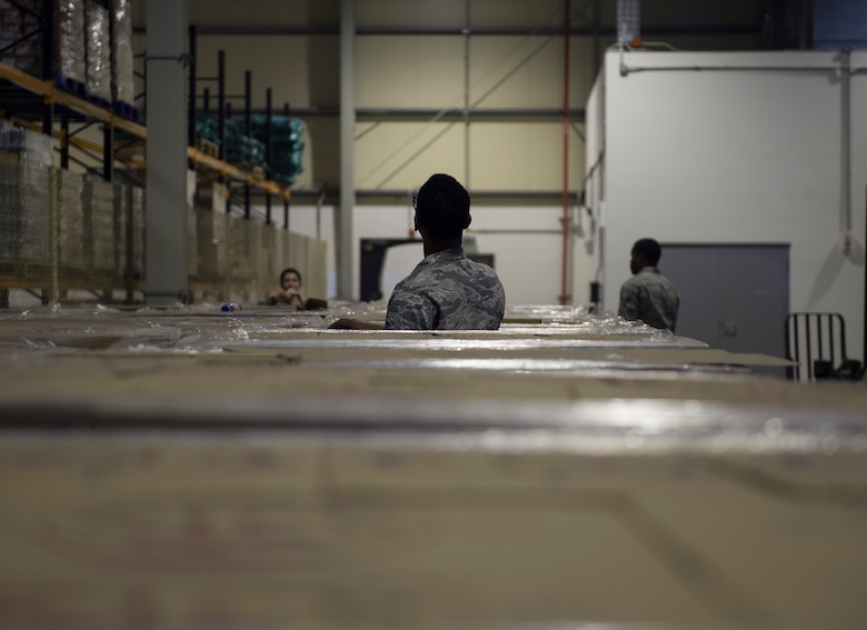 U.S. Air Force Airmen with the 379th Expeditionary Force Support Squadron check the water pallet shipping numbers to ensure the water is safe to drink at Al Udeid Air Base, Qatar, May 10, 2017.  Each week, a small team of Airmen work together to review shipments of produce, making sure the numbers matches the quantity received and that the quality of the produce meets standards. (U.S. Air Force photo by Tech. Sgt. Amy M. Lovgren)