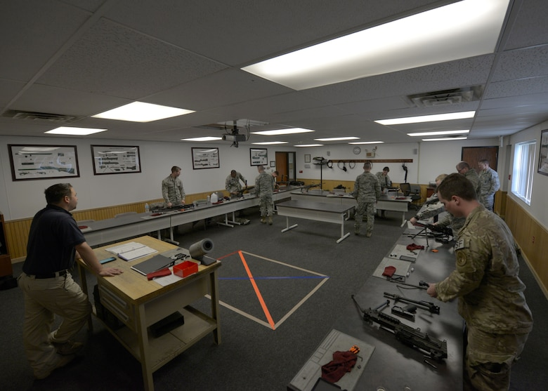 Jeremy Smith, 5th Security Forces Squadron Combat Arms Training and Maintenance instructor, watches Airmen inspect M249 light machine guns at the CATM facility on Minot Air Force Base, N.D., May 8, 2017. Airmen are required to learn proper assembly and disassembly techniques for weapon qualifications. (U.S. Air Force photo/Airman 1st Class Dillon Audit)