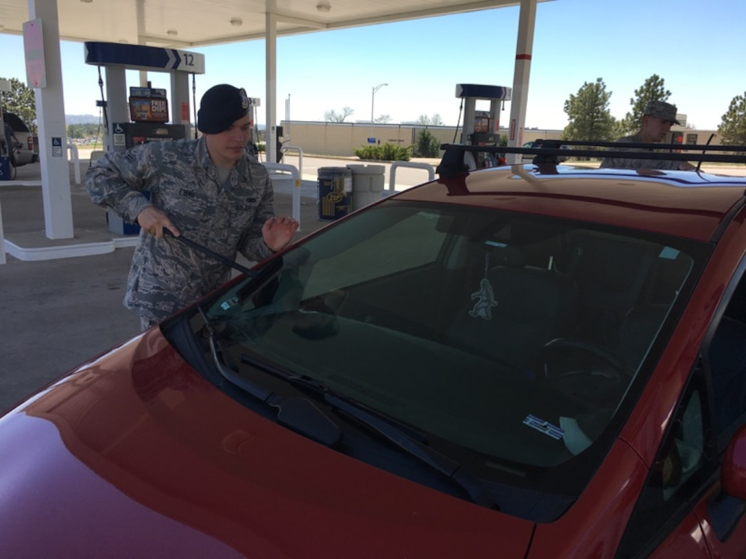 An 10th Security Forces Squadron Defender cleans the windshield of a car at the U.S. Air Force Academy Shopette, May 12, 2017. He and 16 other Defenders raised more than $3,000 for the Air Force Assistance Fund by soliciting donations at the shopette and cleaning customers' windshields. for the AFAF. (Courtesy photo/Chief Master Sgt. Shadd McKee)