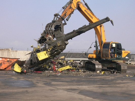 A contractor employs uses an excavator to break up one of 27 OH-58 Kiowa Warrior aircraft at Gimcheon, Korea.