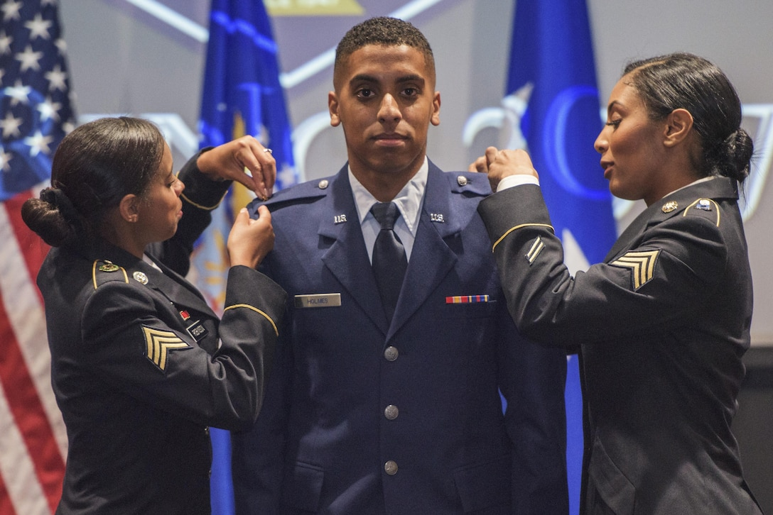 U.S. Air Force 2nd Lt. Jahvon Holmes, University of Texas San Antonio graduate, has his rank pinned on by his sisters May 12, 2017, at UTSA in San Antonio, Texas. Holmes was one of the 17 graduates in attendance, and is the first member of his family to commission in the Air Force who will begin his career in undergraduate pilot training. (U.S. Air Force photo by Senior Airman Stormy Archer)