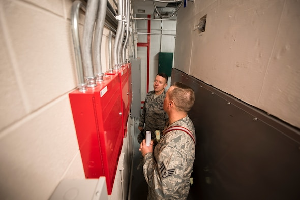 PETERSON AIR FORCE BASE, Colo. – Staff Sgt. Derrick Grinnell, 21st Civil Engineer Squadron fire inspector 2, explains to Chief Master Sgt. Brendan Criswell, Air Force Space Command command chief, the process of inspecting and assessing any fire hazards in a mechanical room at Peterson Air Force Base, Colo., May 11, 2017. Criswell hopes to expand his shadowing program and glimpse into the lives of enlisted members and their duties here on Peterson AFB, as well as other space wings in the command. (U.S. Air Force photo by Airman 1st Class Dennis Hoffman)