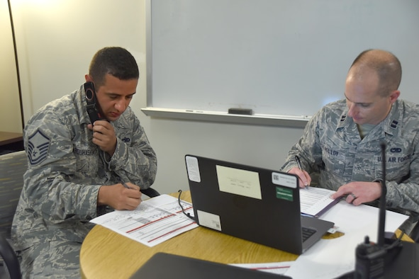 Master Sgt. Mohammed Abouhasem, 22nd Maintenance Squadron production supervisor, left, listens to a phone call during turn over with Capt. Michael Molloy, 22nd MXS operations officer, May 15, 2017, at McConnell Air Force Base, Kan. During turn over, Abouhasem informs Molloy about the status of aircraft. Abouhasem was raised in Doha, Qatar, and has proudly served in the U.S. Air Force for 15 years. (U.S. Air Force photo/Senior Airman Christopher Thornbury)