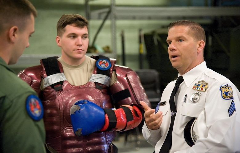 Sergeant Kenneth Gill, Philadelphia Police Department Recruit Training Unit, right, speaks with Senior Airman Nicholas Christopher, left and Staff Sgt. Joshua Floyd, center, both 436th Security Forces Squadron Ravens, May 11, 2017, at Dover Air Force Base, Del. The Airmen conducted a Redman suit training demonstration for their civilian counterparts at the Ravens' training section. (U.S. Air Force photo by Roland Balik)