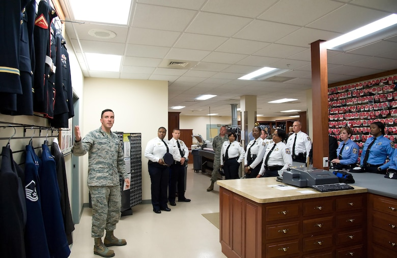 Staff Sgt. Guiseppe Francioni, Air Force Mortuary Affairs Operations uniform section, explains to members of the Philadelphia Police Department, Philadelphia, Pa., all the service uniforms carried in the section for fallen service members, May 11, 2017, at AFMAO on Dover Air Force Base, Del. Francioni mentioned that fallen service members are provided brand-new dress uniforms with all the proper decorations and medals prior to departing AFMAO. (U.S. Air Force photo by Roland Balik)
