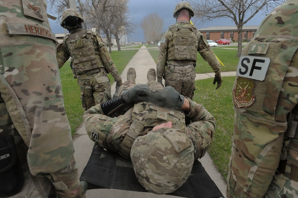 Members of the 91st Security Forces Group Global Strike Challenge team litter-carry a teammate during training at Minot Air Force Base, N.D., May 1, 2017. The team practiced physical fitness with buddy carries, a Humvee push and the litter carry. (U.S. Air Force photo/Airman 1st Class Jessica Weissman)