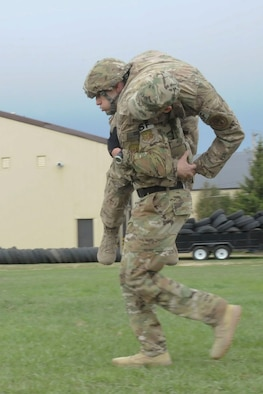 Tech. Sgt. Kyle Douglass, 91st Security Forces Group physical security NCO in charge, buddy carries a teammate during training at Minot Air Force Base, N.D., May 1, 2017. The team practiced physical fitness with buddy carries, a Humvee push and a liter carry. (U.S. Air Force photo/Airman 1st Class Jessica Weissman)