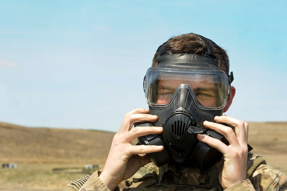 Airman Ryan Benjamin, 91st Missile Security Forces Squadron response force member, puts on a gas mask at Camp Grafton South, Devil's Lake, N.D., May 4, 2017. The 91st Security Forces Group Global Strike Challenge team trained in preparation for the upcoming competition, which challenges security forces tactics, job knowledge and weapons firing. (U.S. Air Force photo/Airman 1st Class Jessica Weissman)