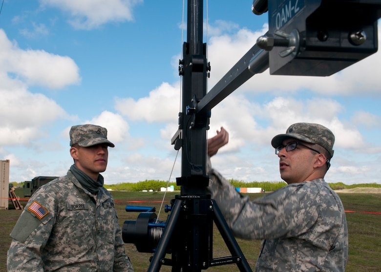 Pfc. Ismael Torres, a cable system installer maintainer, left, and Spc. Cody Gomez, a microwave system operator maintainer, prepare to raise a transmission antenna during Exercise Maple Resolve 17 at Camp Wainwright, Alberta, May 16, 2017. Torres and Gomez, both California natives, belong to the 306th Psychological Operations Company. Exercise Maple Resolve is an annual collective training event designed for any  contigency operation. Approximately 4,000 Canadian and 1,000 U.S. troops are participating in Exercise Maple Resolve 17.