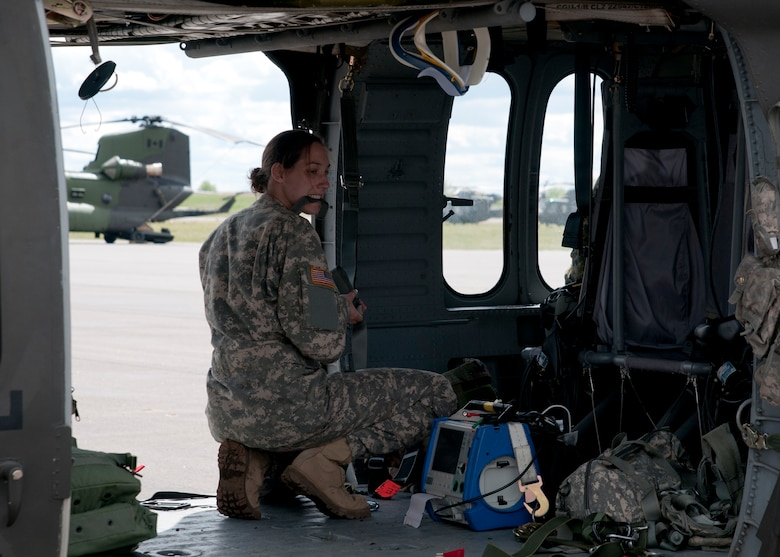 Sgt. Rebecca Himmel, a medic attached to the 1-169th Aviation Regiment, readies medical equipment and her personal gear aboard a Blackhawk helicopter prior to performing a joint medevac training mission during Exercise Maple Resolve 17 at Camp Wainwright, Alberta, May 16, 2017. Exercise Maple Resolve is an annual collective training event designed for any  contigency operation. Approximately 4,000 Canadian and 1,000 U.S. troops are participating in Exercise Maple Resolve 17.