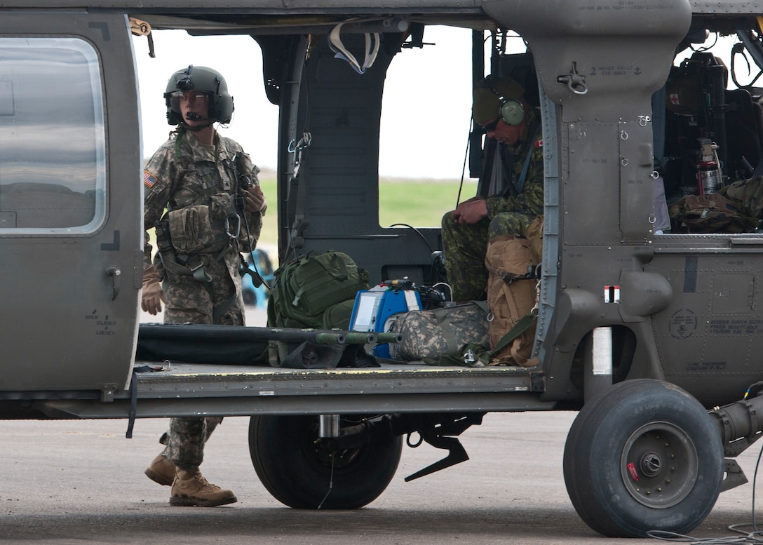 Sgt. Rebecca Himmel, a medic attached to the 1-169th Aviation Regiment, and Canadian Cpl. Jason Flegel, a forward aeromedevac specialist with the 2nd Field Ambulance, prepare to embark on a joint medevac training mission during Exercise Maple Resolve 17 at Camp Wainwright, Alberta, May 16, 2017. Exercise Maple Resolve is an annual collective training event designed for any  contigency operation. Approximately 4,000 Canadian and 1,000 U.S. troops are participating in Exercise Maple Resolve 17.
