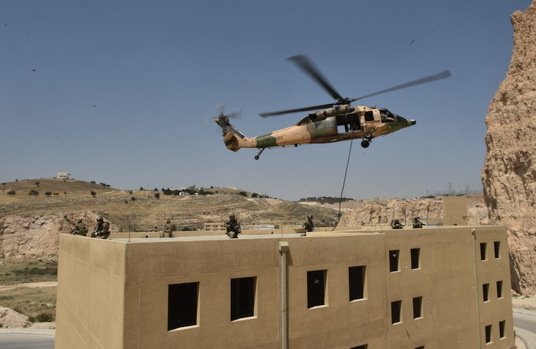 Italian special operations forces, U.S. Air Force Special Tactics and members of the Jordanian Armed Forces Special Task Force fast rope from a Royal Jordanian Air Force UH-60L Blackhawk helicopter onto a three-story building during Exercise Eager Lion May 11, 2017, at King Abdullah II Special Operations Training Center. Eager Lion is an annual U.S. Central Command exercise in Jordan designed to strengthen military-to-military relationships between the U.S., Jordan and other international partners. This year's iteration is comprised of about 7,200 military personnel from more than 20 nations that will respond to scenarios involving border security, command and control, cyber defense and battlespace management. (U.S. Air Force photo by Senior Airman Ryan Conroy)