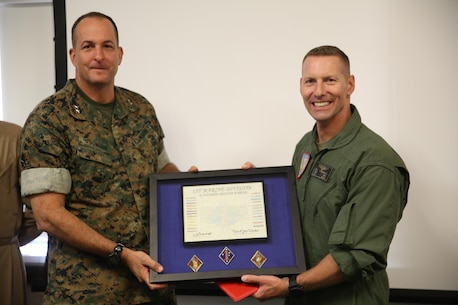 Maj. Gen. Daniel O'Donohue, left, 1st Marine Division commanding general, awards Col. Michael Borgschulte, right, commanding officer of Marine Aircraft Group (MAG) 39, a certificate of honorary membership at Marine Corps Air Station Camp Pendleton, Calif., May 15. 1st MARDIV recognized MAG-39 as an honorary member for continuing to support I MEF ground Marines and continuously working toward more advanced Marine air-ground task force integration. (U.S. Marine Corps photo by Lance Cpl. Jake M.T. McClung/Released)