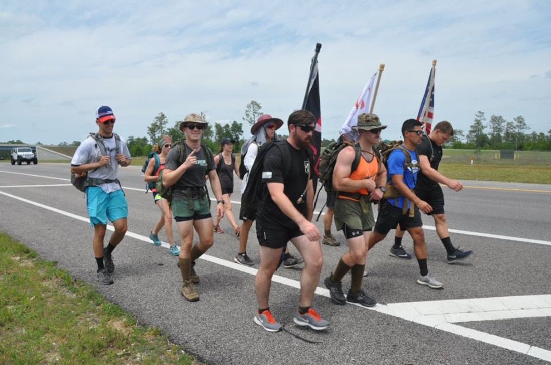 Marines, Sailors and Midshipmen from Auburn University make their way past the entrance to Duke Field, Fla. May 9 during their recent 201-mile journey from their campus headquarters to the Black Hawk memorial in Navarre, Fla.  The ruck marchers made the trip to honor the memory of Raider 7, an elite group of Marine Raiders who perished in a helicopter training accident in Navarre March 10, 2015.  (U.S. Air Force photo/Dan Neely)