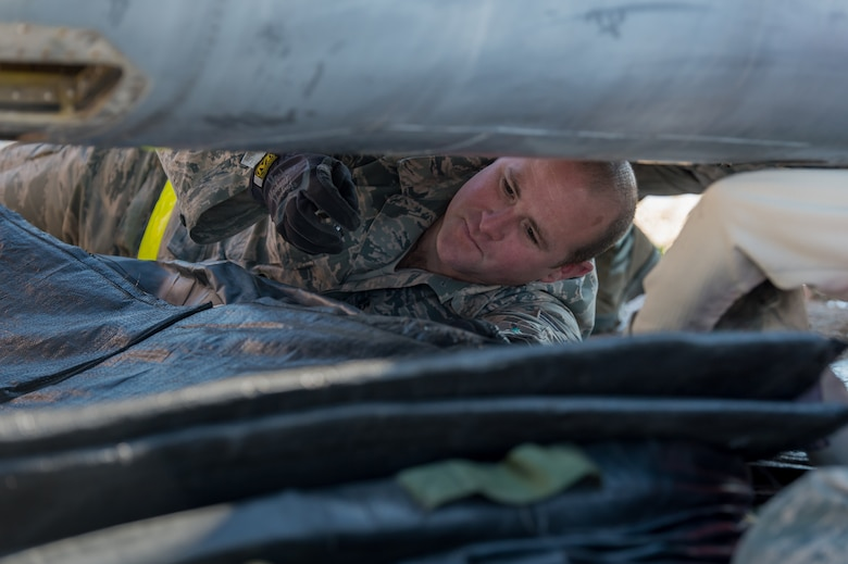U.S. Air Force Tech. Sgt. Jeremy Mullin, aircraft fuel system specialist with the 153rd Maintenance Group's Crash Damage or Disabled Aircraft Recovery team configures an air bag for inflation prior to jacking an A-7 Corsair II aircraft, May 11, 2017 in Cheyenne, Wyoming. Maintainers from all aircraft specialties practiced moving a fighter aircraft from the mud into a parking spot as part of an annual CDDAR requirement. (U.S. Air National Guard photo by Senior Master Sgt. Charles Delano/released)