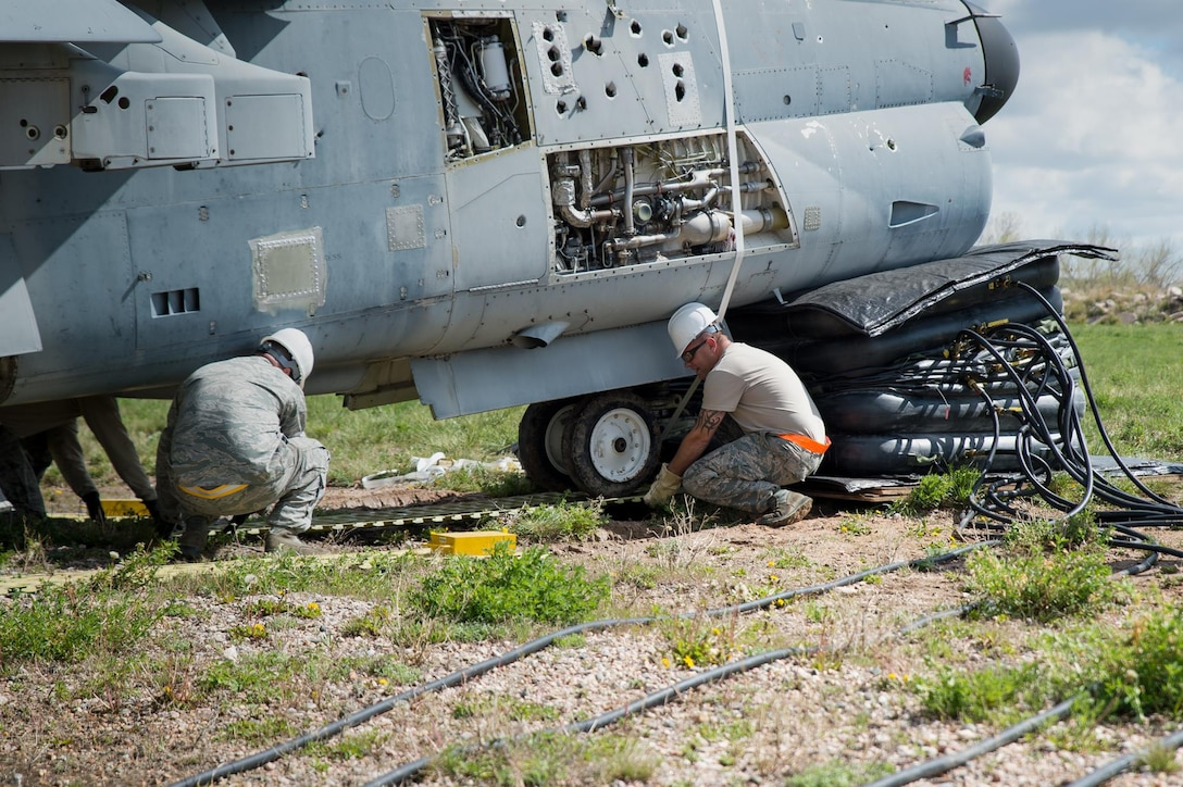 U.S. Air Force Tech. Sgt. Sean Quinlan and Staff Sgt. Aaron Berning with the 153rd Maintenance Group's Crash Damage or Disabled Aircraft Recovery team place steel planking beneath the front landing gear of an A-7 Corsair II aircraft, May 11, 2017 in Cheyenne, Wyoming. Maintainers from all aircraft specialties practiced moving a fighter aircraft from the mud into a parking spot as part of an annual CDDAR requirement. (U.S. Air National Guard photo by Senior Master Sgt. Charles Delano/released)